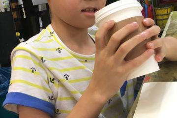 Kind mit Kaffeebecher